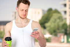 Portrait of a happy sports man standing near  sport field   with a mobile phone  outdoors Royalty Free Stock Photos