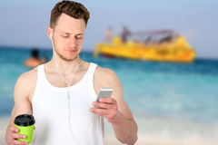 Portrait of a happy sports man standing near  sport field   with a mobile phone  outdoors Royalty Free Stock Image