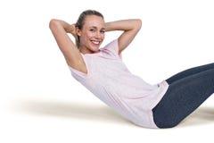 Portrait of happy sporty woman doing sit ups Stock Photo