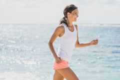 Happy sporty woman jogging with skies and sea at the background royalty free stock photo