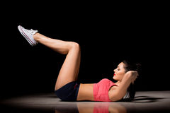 Portrait of happy sporty woman making abs exercise. Joyful female model training indoors. Healthy active lifestyle Royalty Free Stock Photography
