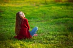 Portrait of happy sporty woman relaxing in park on green meadow. Joyful female model breathing fresh air outdoors. Portrait of happy sporty woman relaxing in Royalty Free Stock Photos