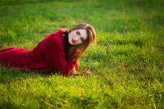 Portrait of happy sporty woman relaxing in park on green meadow. Joyful female model breathing fresh air outdoors Royalty Free Stock Photo