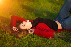 Portrait of happy sporty woman relaxing in park on green meadow. Joyful female model breathing fresh air outdoors Royalty Free Stock Images