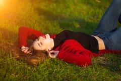 Portrait of happy sporty woman relaxing in park on green meadow. Joyful female model breathing fresh air outdoors. Portrait of happy sporty woman relaxing in Royalty Free Stock Images