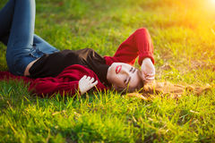 Portrait of happy sporty woman relaxing in park on green meadow. Joyful female model breathing fresh air outdoors Royalty Free Stock Photography