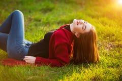 Portrait of happy sporty woman relaxing in park on green meadow. Joyful female model breathing fresh air outdoors. Portrait of happy sporty woman relaxing in Royalty Free Stock Photography