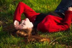Portrait of happy sporty woman relaxing in park on green meadow. Joyful female model breathing fresh air outdoors Royalty Free Stock Image