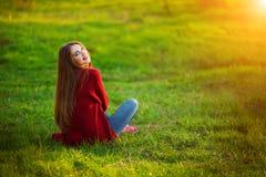 Portrait of happy sporty woman relaxing in park on green meadow. Joyful female model breathing fresh air outdoors. Portrait of happy sporty woman relaxing in Stock Image