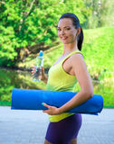 Portrait of happy sporty woman with yoga mat and water in park Stock Photography