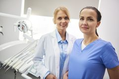 Portrait of happy stomatologist and her dental assistant. In medical uniform royalty free stock images