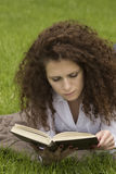 Portrait of happy student relaxed outdoors reading Royalty Free Stock Images