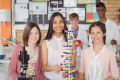Portrait of happy students experimenting molecule model in laboratory Royalty Free Stock Images