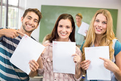 Portrait of happy students pointing at papers Stock Images