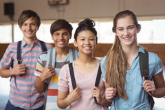 Portrait of happy students standing with schoolbags in campus Stock Image