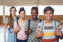 Portrait of happy students standing with schoolbags in campus Royalty Free Stock Image