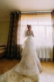 Portrait of happy stylish brlonde bride in veil and luxury long white dress standing near the window Stock Photography