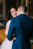 Portrait of happy stylish newlywed couple kissing at luxurious vintage interior Royalty Free Stock Photo