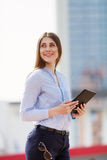 Portrait of happy successful businesswoman in blue shirt holding touch pad and smiling Stock Image