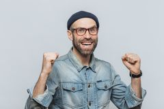 Portrait of happy successful man rejoices his triumph, clenches royalty free stock images