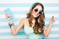 Portrait happy summer mood of joyful young woman with long curly hair, in sunglasses, heels having fun on striped. Background. Blue colors, expressing stock photos