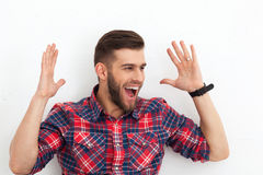 Portrait of happy surprised handsome young man against white wal Stock Photography