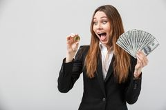 Portrait of happy surprised lady looking at golden bitcoin in hand isolated Royalty Free Stock Image