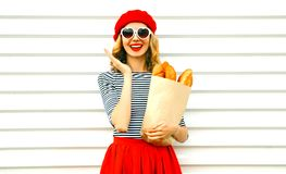 Portrait happy surprised laughing woman wearing red beret holding paper bag with long white bread baguette on white. Wall background royalty free stock image