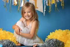 Portrait of happy surprised little girl in princess dress with open mouth and waving hands isolated on blue background royalty free stock images