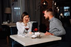 Portrait of happy and surprised young woman receiving present from boyfriend while sitting in cafe. Love, romance, valentines day, couple and people concept Stock Photo