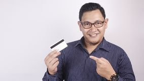 Happy Young Man Smiling and Pointing Credit Card royalty free stock photography