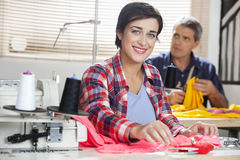 Portrait Of Happy Tailor Stitching At Workbench Royalty Free Stock Photo