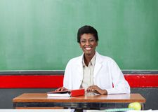 Portrait Of Happy Teacher Sitting At Desk In Royalty Free Stock Photo