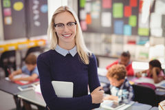 Portrait of happy teacher standing with arms crossed in classroom. At school Royalty Free Stock Image
