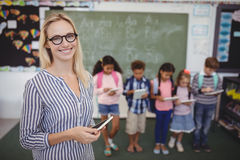 Portrait of happy teacher standing holding digital tablet. With students in background Royalty Free Stock Photos