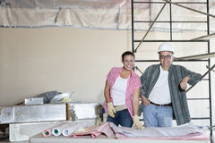 Portrait of happy team of architects with building plans at construction site Stock Image