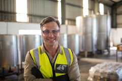 Portrait of happy technician standing with arms crossed. In oil factory Royalty Free Stock Images