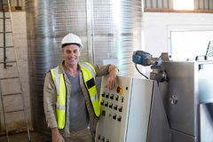 Portrait of happy technician standing near machine. In oil factory Royalty Free Stock Image