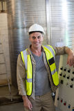 Portrait of happy technician standing near machine. In oil factory Royalty Free Stock Photography