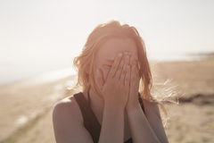 Portrait of happy teen girl on beach closing her. Face with hands, summer photo Stock Image