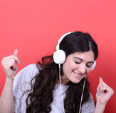 Portrait of happy teen girl dancing and listening music against Stock Photos