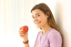 Teen holding an apple and looking at you. Portrait of a happy teen holding an apple and looking at you leaning on a wall in a house interior Stock Photo