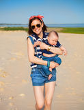 Portrait of happy teen sister and little baby brother. On the beach Stock Photos