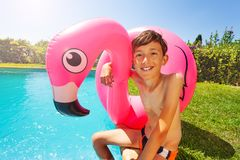 Happy boy with swim ring relaxing by the pool. Portrait of happy teenage boy with flamingo inflatable ring relaxing by the swimming pool in summer royalty free stock photography