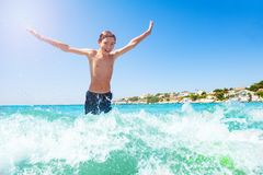 Happy teenage boy jumping in shallow water wave royalty free stock images