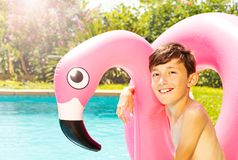 Boy with swim ring at the edge of swimming pool stock image