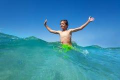 Happy teenage boy standing waist deep in sea water royalty free stock images