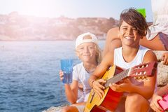 Young musician plays guitar at outing with friends. Portrait of happy teenage boy, young musician, playing guitar during outing with friends at the seaside stock photography