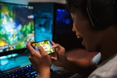 Portrait of happy teenage gamer boy playing video games on smart. Phone and computer in dark room wearing headphones and using backlit colorful keyboard royalty free stock photos