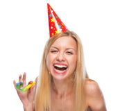 Portrait of happy teenage girl in cap with party horn blower Royalty Free Stock Photography
